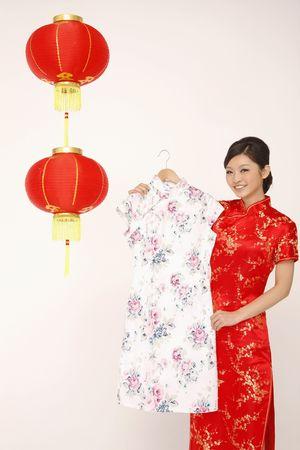 Woman holding cheongsam on coat hanger photo