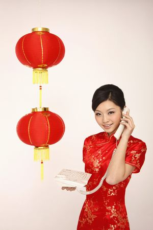 cheongsam: Woman in red cheongsam talking on the phone