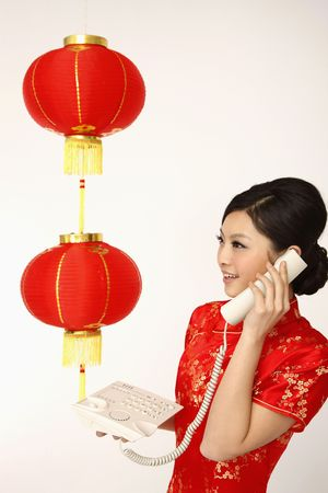 Woman in red cheongsam talking on the phone photo