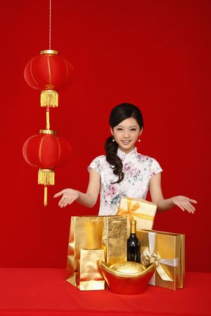 cheongsam: Woman showing the variation of gifts on the table Stock Photo