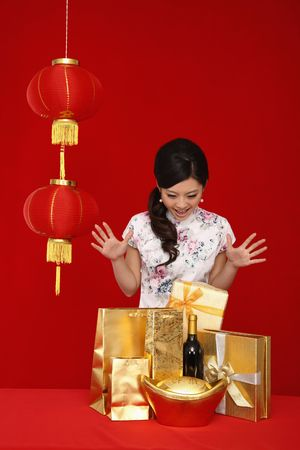 Surprised woman looking at the variation of gifts on the table Stock Photo
