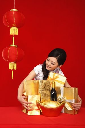 chinese new year food: Woman posing with gifts on the table Stock Photo