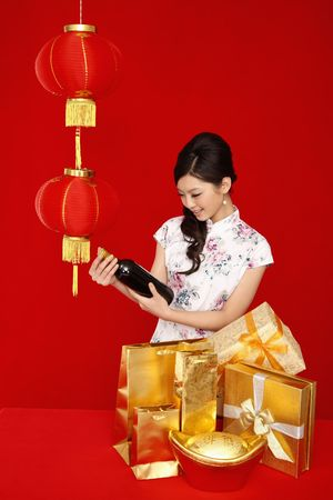 Woman in cheongsam checking out bottle of wine Stock Photo