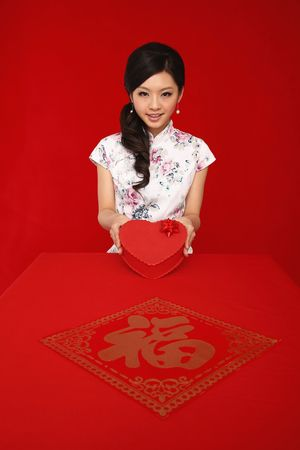 Woman in cheongsam holding heart shaped gift box photo
