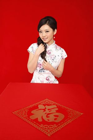 Woman in cheongsam playing with her hair Stock Photo