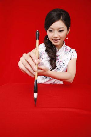 Woman in cheongsam writing New Years greeting