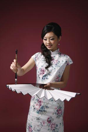 Woman writing New Years greeting on fan photo