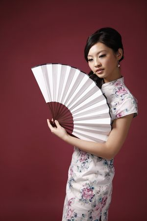 Woman in cheongsam holding fan Stock Photo