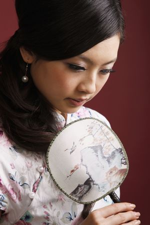 Woman in cheongsam holding fan while contemplating photo