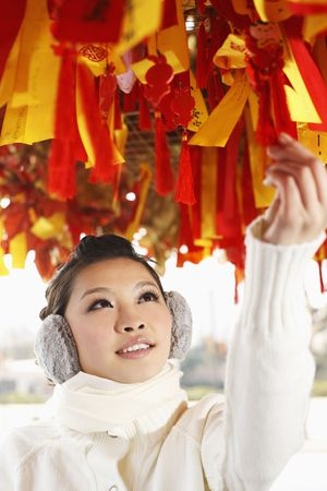 muff: Woman reading wishes on the hanging ribbons