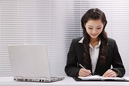 Woman smiling while writing photo