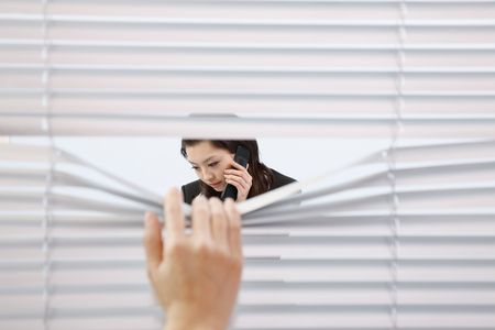 Hand pulling blinds, woman talking on the phone Stock Photo