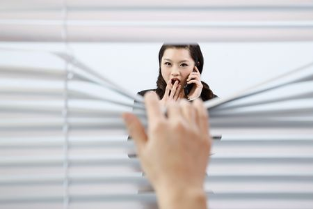 Hand pulling blinds, woman in shock while talking on the phone photo