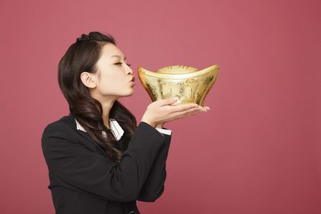 women kissing women: Woman with eyes closed about to kiss gold ingot