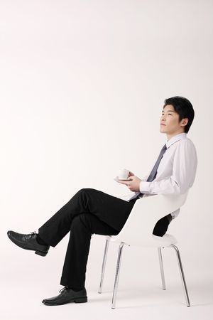 Man relaxing on chair, holding a cup of coffee Stock Photo