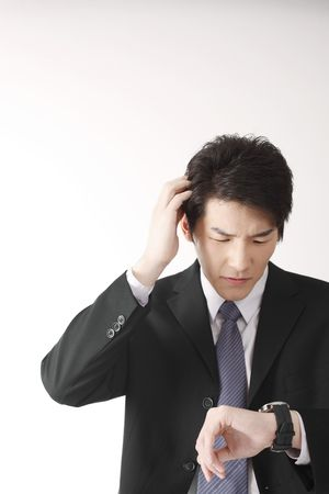scratching head: Man scratching head while checking time on his watch