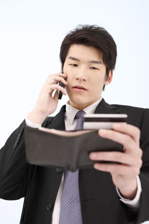 Man referring to his credit card while talking on the phone photo