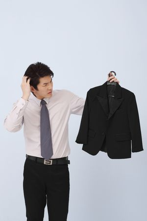 Man scratching head while looking at suit on coathanger Stock Photo - 4780397