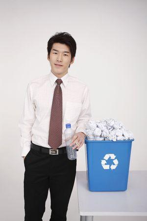 kunststof fles: Man met plastic fles, permanent naast prullen bak