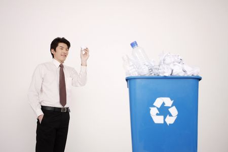 throw paper: Man trying to throw crumpled paper into recycle bin Stock Photo