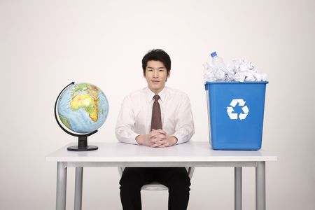 Man sitting with globe and recycle bin on the table Stock Photo - 4778468