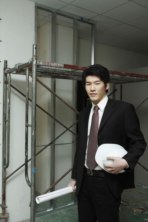 Man holding safety helmet and blueprint photo