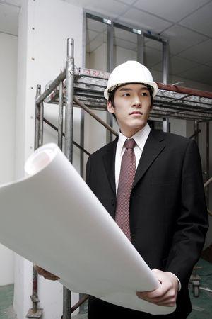 Man with safety helmet reading blueprint photo
