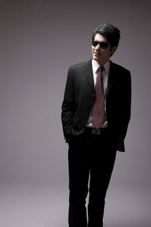 Man in full suit with sunglasses standing with his hands in pocket Stock Photo - 10295756
