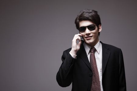Man in full suit with sunglasses talking on the phone photo