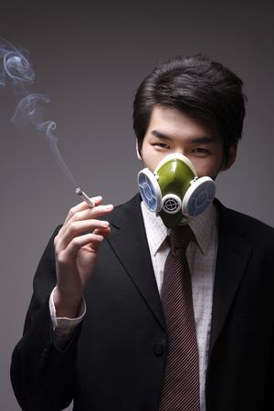 Man with gas mask smoking cigarette photo