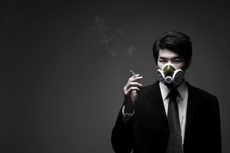 Man with gas mask smoking cigarette Stock Photo - 10295688