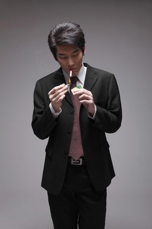 man front view: Man lighting up cigarette