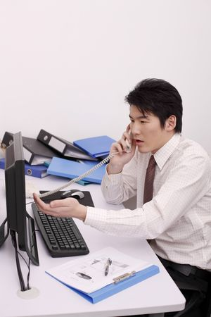 mousepad: Man looking at computer monitor while talking on the phone Stock Photo