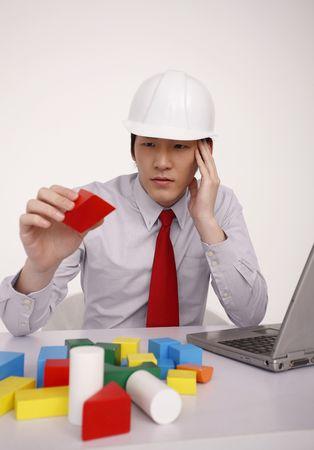 safety helmet: Hombre con casco de seguridad de jugar con bloques de madera Foto de archivo