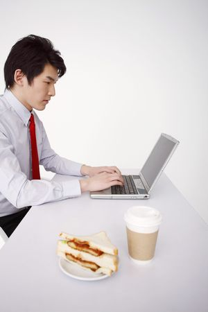 Man using laptop, sandwich and coffee beside him photo
