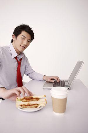 Man taking sandwich while using laptop photo