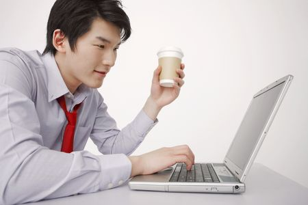 Man holding a cup of coffee while using laptop photo