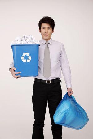 recyclage plastique: Homme tenant une poubelle de papiers froiss�s et un sac en plastique