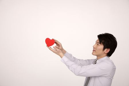 Man showing a red heart shaped box