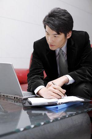 Man writing on organizer while looking at laptop photo