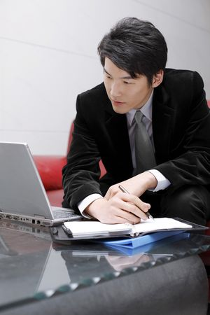 Man writing on organizer while looking at laptop