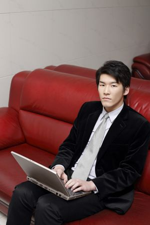 Man sitting on couch using laptop photo