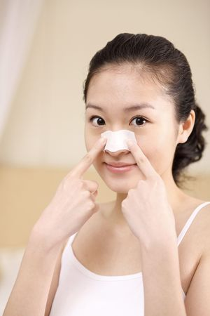 Young woman applying nose strip on her nose photo