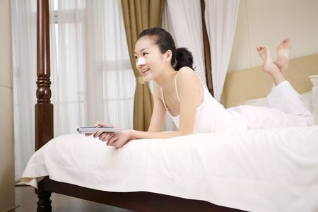 Young woman with nose strip on her nose lying forward on the bed watching television Stock Photo - 10294191