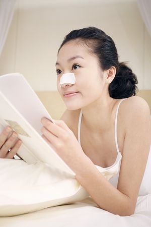 lying forward: Young woman with nose strip lying forward on the bed reading book Stock Photo