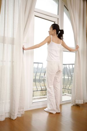 Young woman standing in doorway to balcony Stock Photo