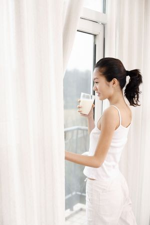 Young woman standing in doorway to balcony drinking a glass of milk