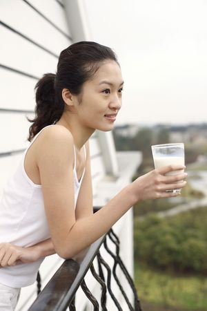 Young woman standing at the balcony holding a glass of milk