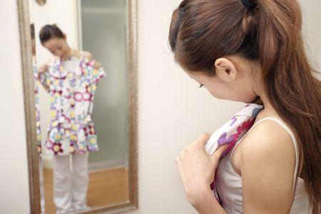 vistiendose: Joven mujer con vestido al estar de pie delante del espejo Foto de archivo