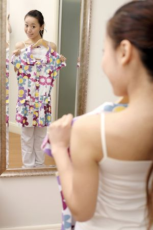 Young woman holding dress while standing in front of mirror photo